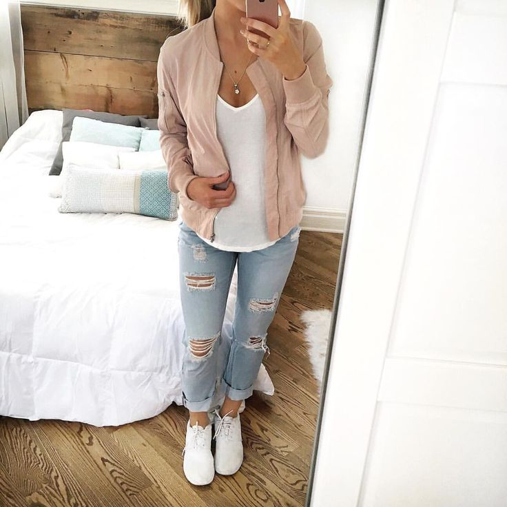 Blush pink bomber jacket over white tee, light wash ripped jeans and white sneak...