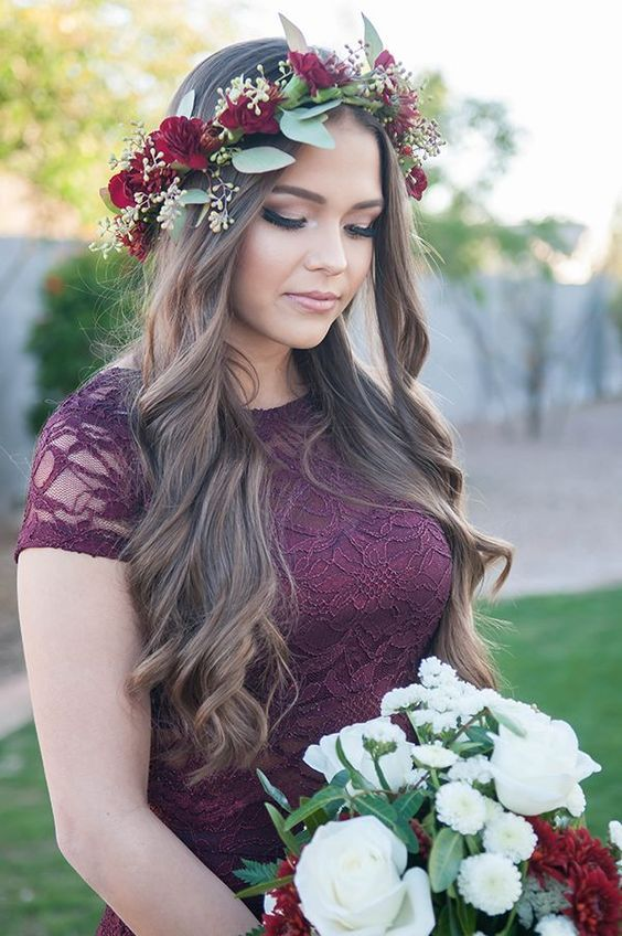 Bridesmaid wearing a burgundy lace dress and a jewel-toned floral crown made out...