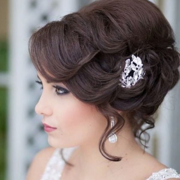 A Wonderful chignon with soft waves and curls lightly teased from it to give a r...