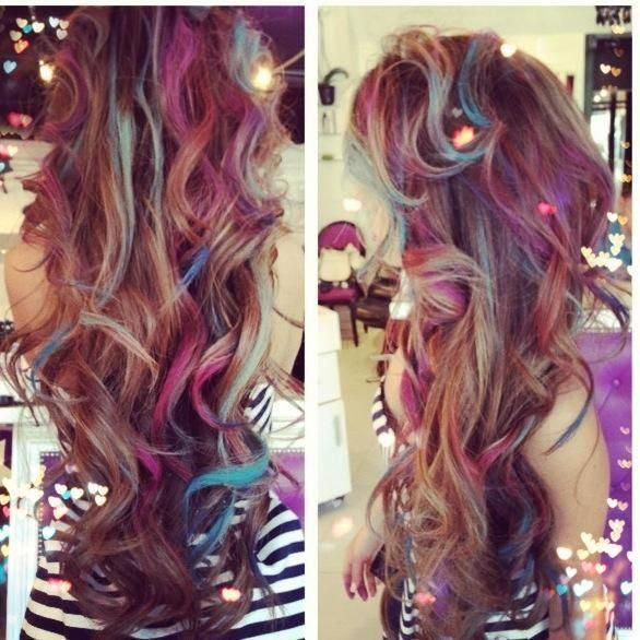 Messy brown curls, with strands of hair streaked with pastel hair chalk