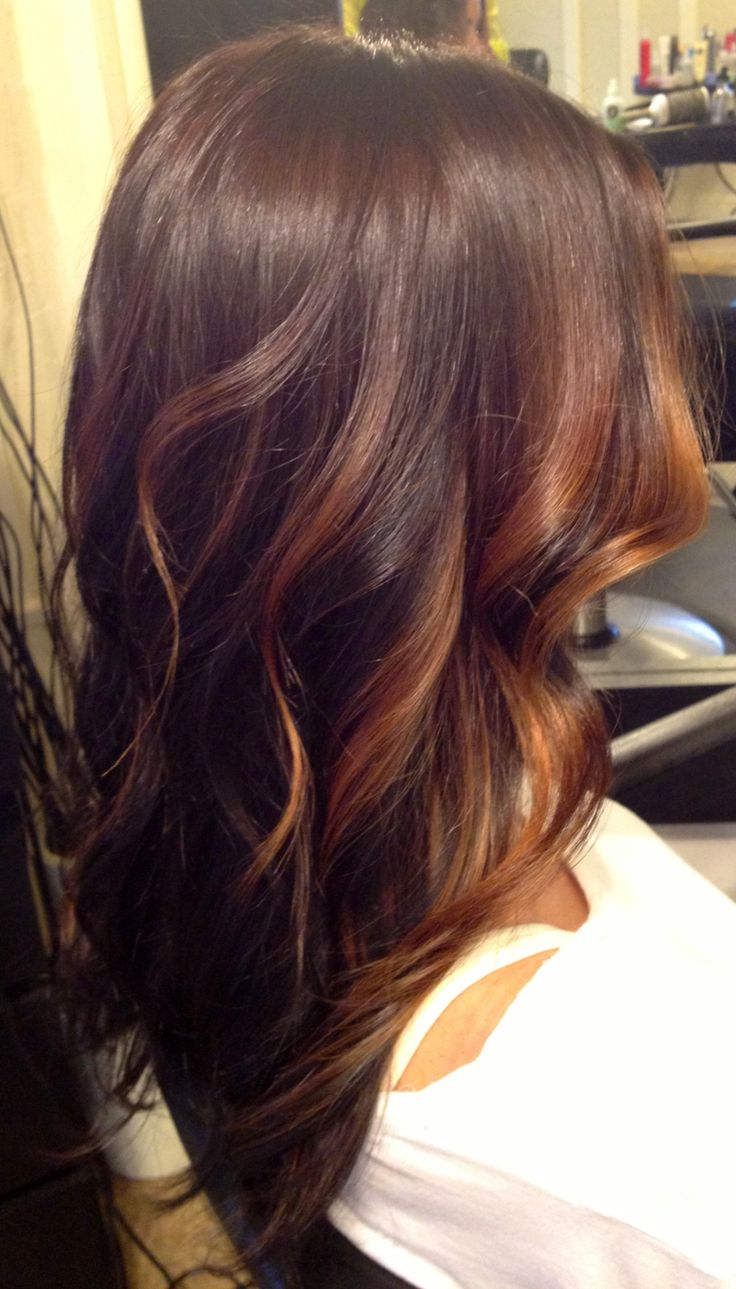 Brunette and Caramel face framing Balayage highlights over long layered curly ha...